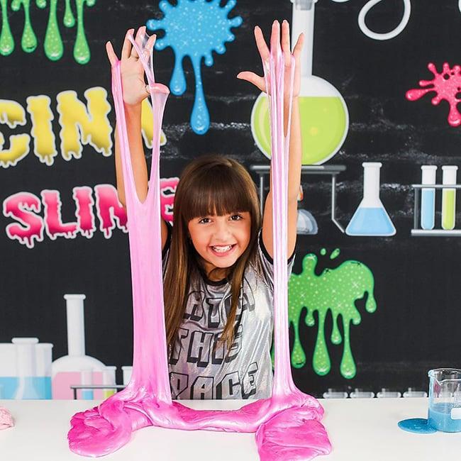 Niña jugando con slime de color rosa