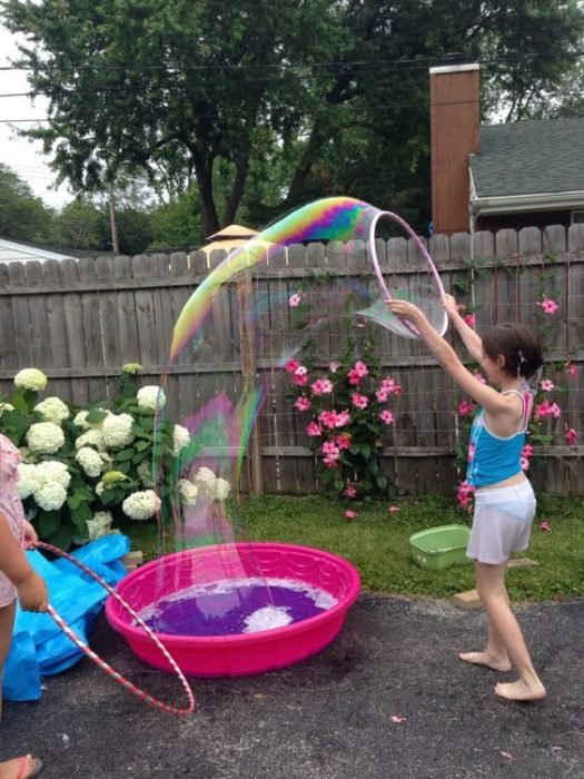 Niña jugando con burbujas gigantes