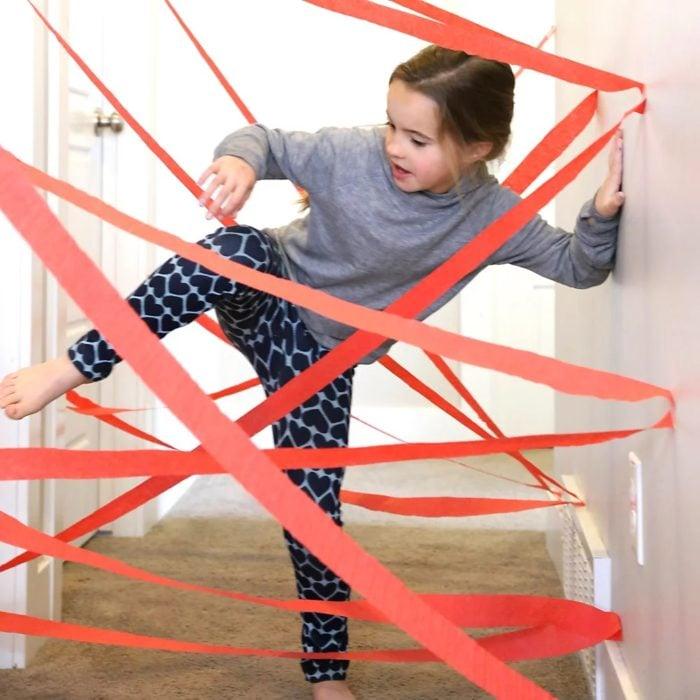 Niña jugando carrera de obstáculos en casa