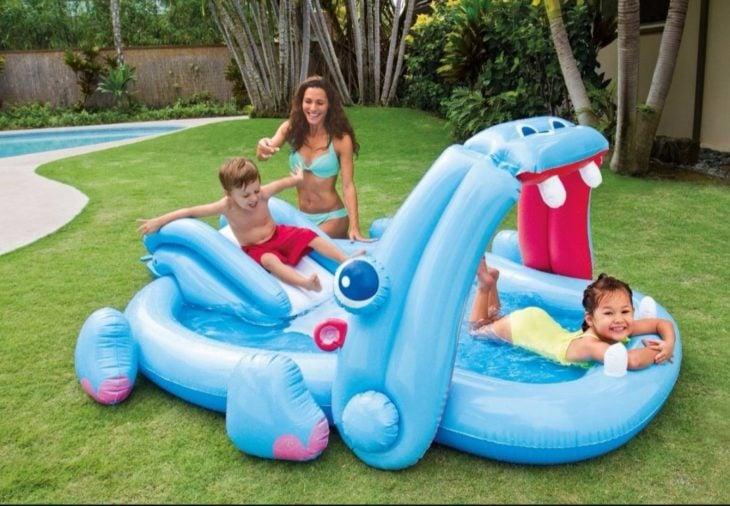 Mujer junto a asus hijos jugando en una alberca inflable