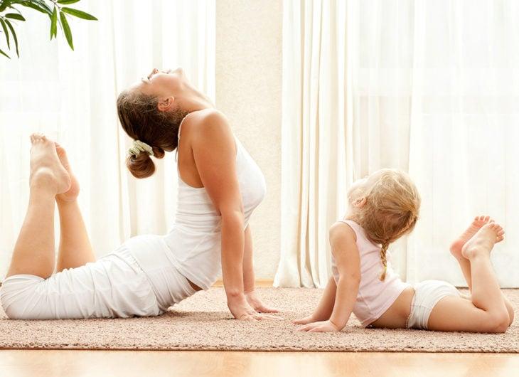Madre e hija haciendo yoga en su sala