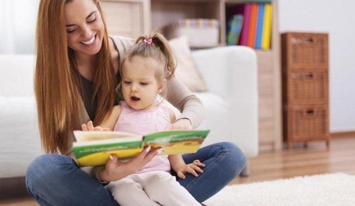 Mujer cargando a su bebé y contándole un cuento