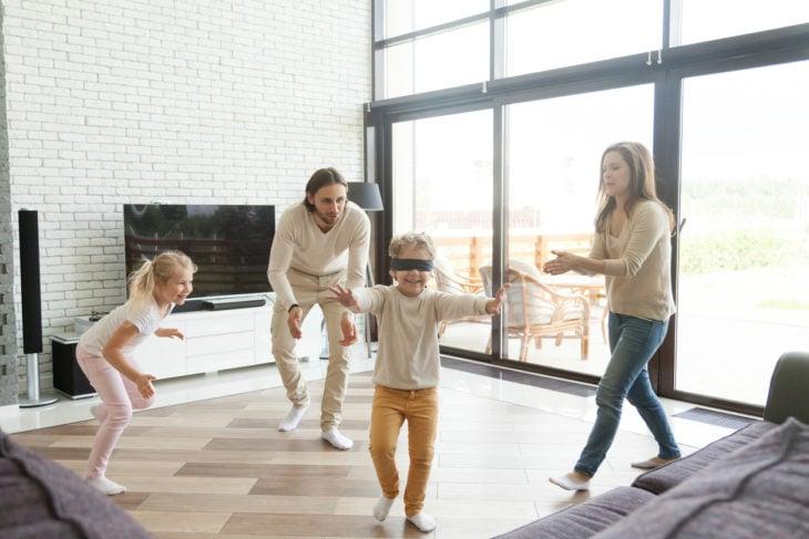 Familia jugando escondidillas con una venda en los ojos