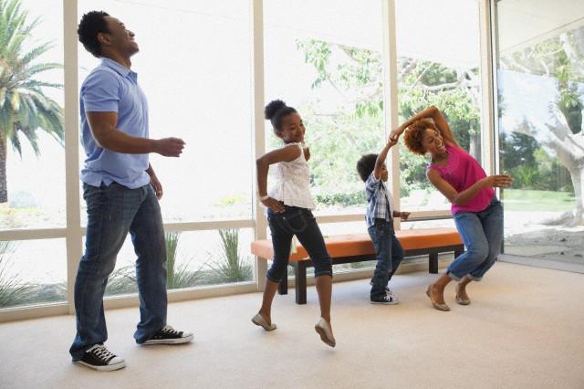 Familia realizando juego de baile en la sala de su casa