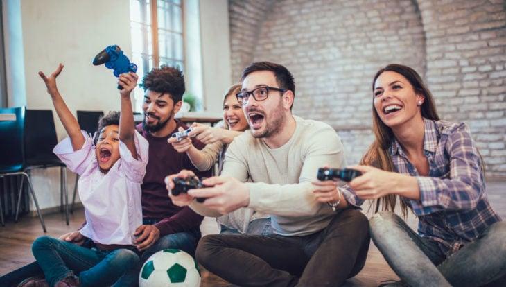 Familia reunida jugando videojuegos en la sala