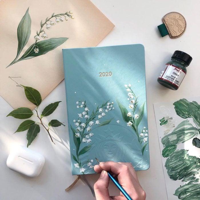 Agenda en tono azul con pintura en diseño de hojas y flores blancas