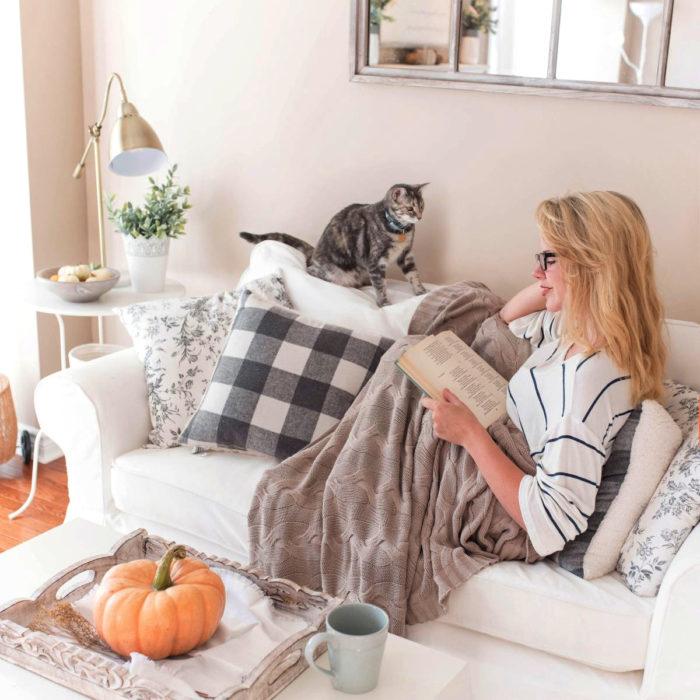 Mujer rubia leyendo libro en el sillón con su gato