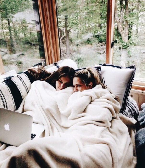 Amigas recostadas en sofá viendo una película