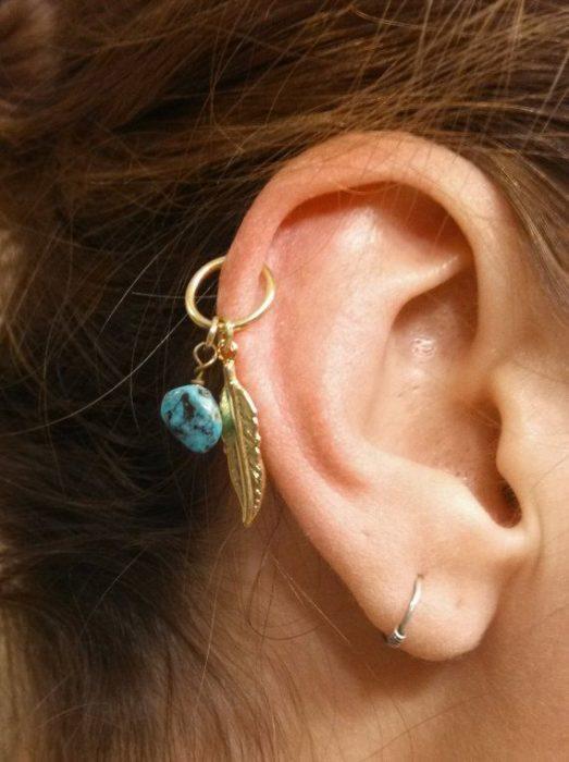 Arete para oreja con dije de pluma y piedra azul
