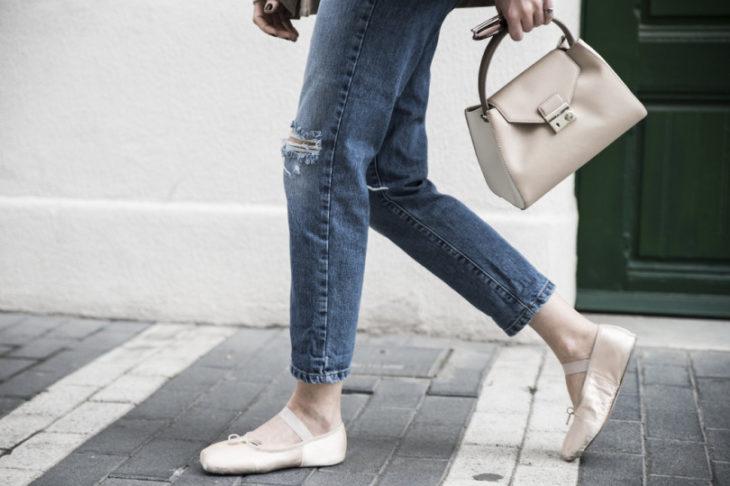 Piernas de mujer van por la calle con jeans y bailarinas rosa palo