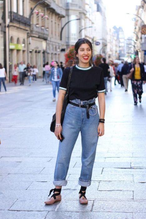 Chica sonríe y viste jeans azules con blusa negra y bailarinas rosas con lazos negros