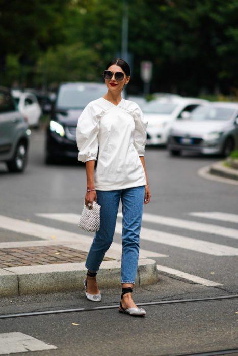 Mujer cruza la calle con blusa blanca y jeans oscuros mientras usa bailarinas blancas