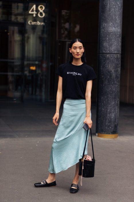 Mujer asiática con cabello recogido posa con falsa azul, blusa negra y bailarinas negras