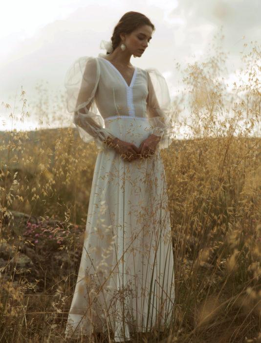 Mujer en pastizal con vestido de novia marfil de mangas gigot