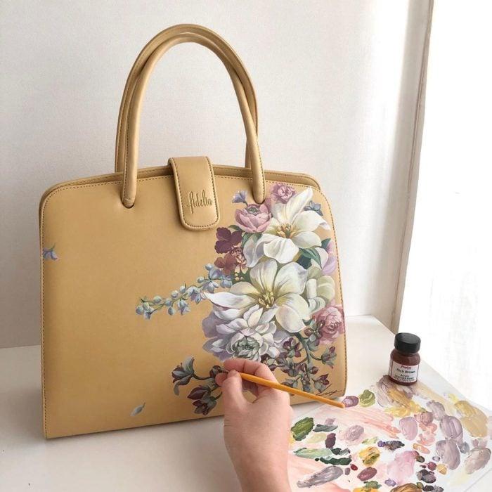 Bolsa de mano amarilla con flores pintadas a mano