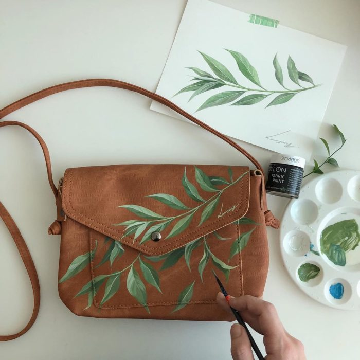 Bolsa de mano color camel con diseño de hojas color verde