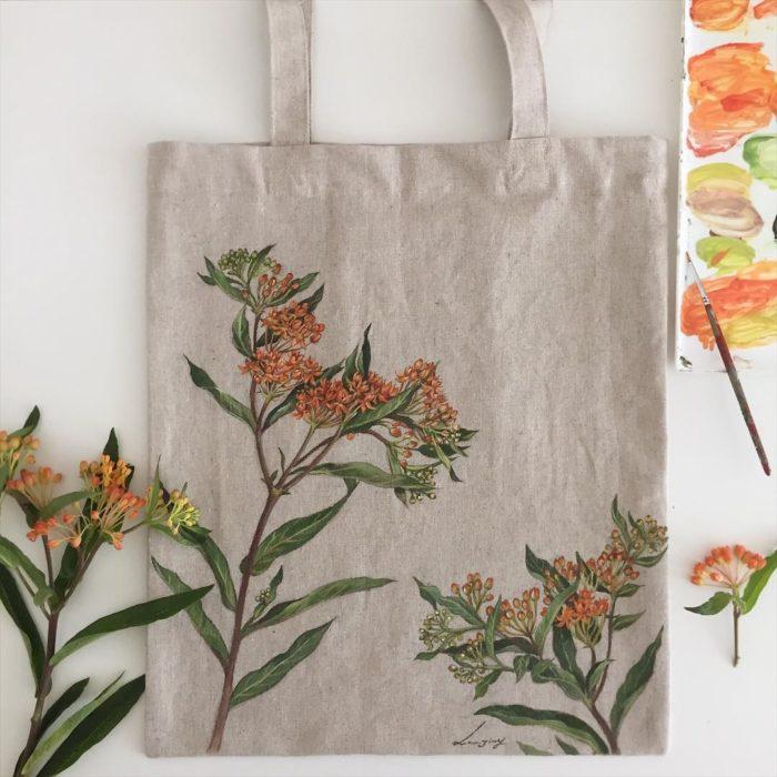 Bolsa tipo loneta color beige con hojas y flores cafés/marrón