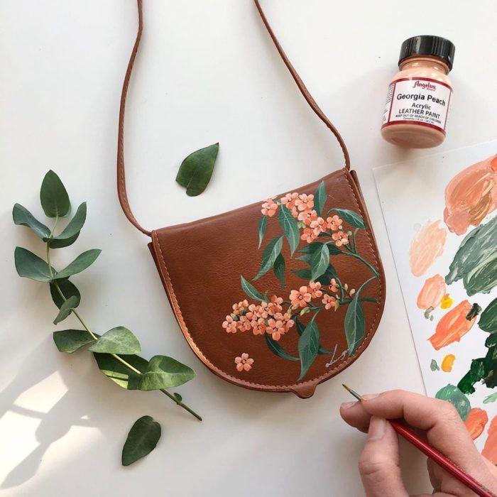 Bolsa de mano color café con hojas verdes y flores color coral