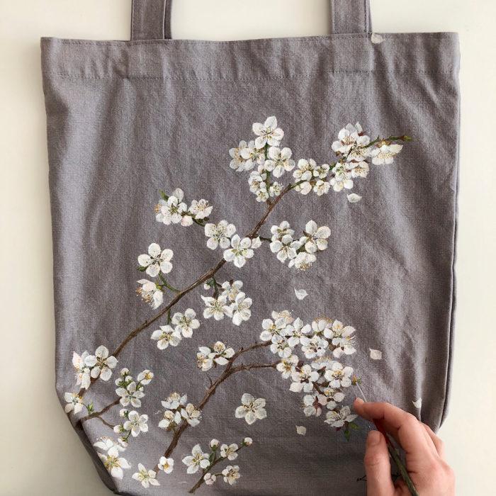 Bolsa tipo loneta color gris con hojas y flores blancas
