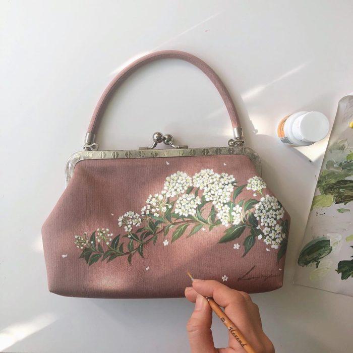 Bolsa de mano color rosa palo con hojas verdes y flores pequeñas blancas