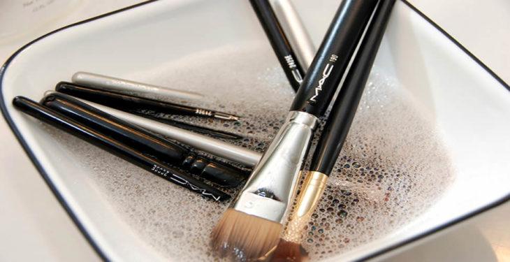 Brochas de maquillaje en recipiente con agua