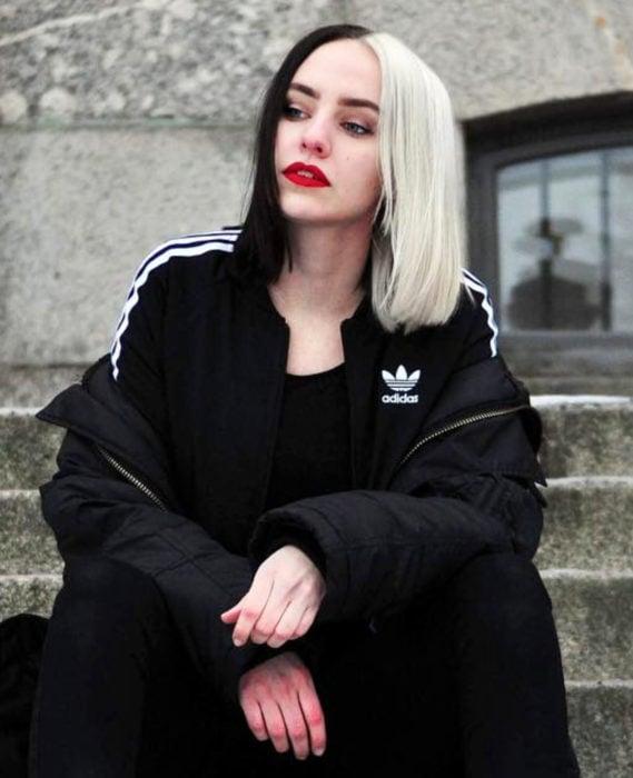 Cabello negro con blanco; chica sentada en escaleras con tinte bicolor, teñido mitad oscuro y mitad blanco