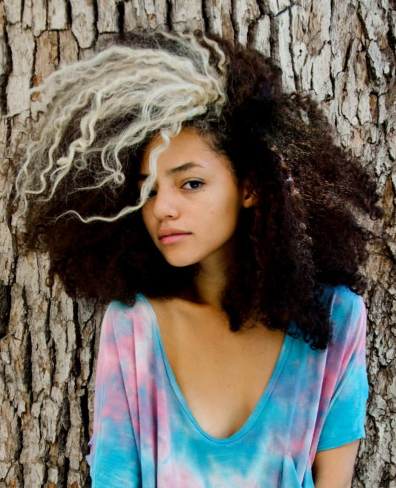 Cabello negro con blanco; chica afroamericana con cabello chino y un mechón rubio