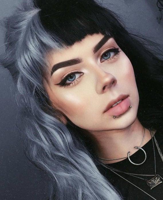 Cabello negro con blanco; chica de ojos azules con maquillaje natural, piercings en el labio, tinte bicolor, oscuro y gris, copete disparejo