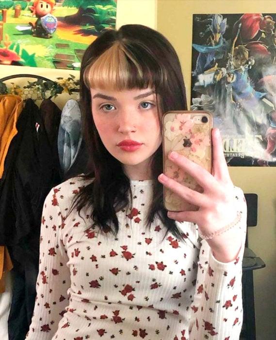 Cabello negro con blanco; chica tomándose selfie frente a espejo, cabello lacio con copete con un mechón rubio