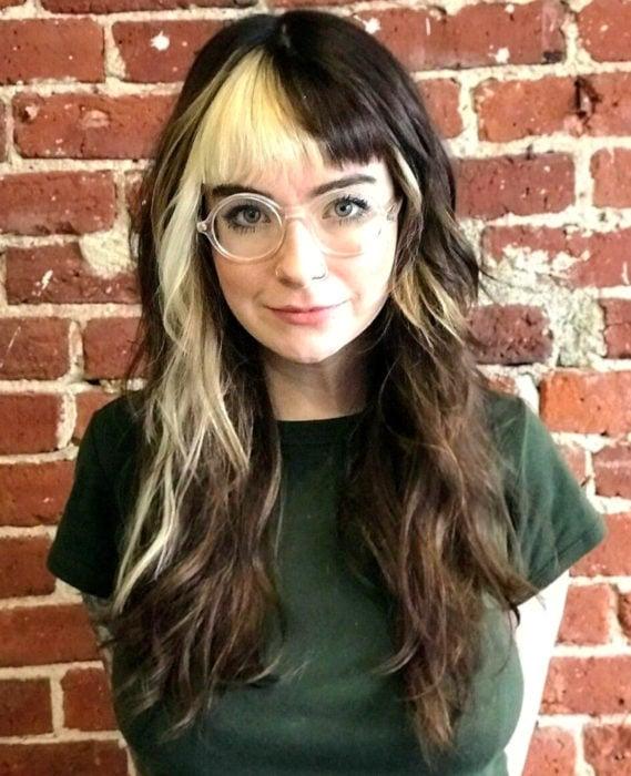 Cabello negro con blanco; chica de cabello largo, ondulado, con fleco mitad castaño y rubio