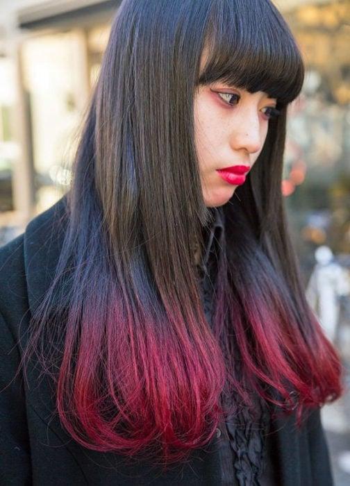 Chica asiática con cabello largo y puntas rojas