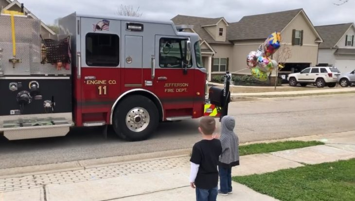 Scot Michael's saludando un camión de bomberos fuera de su casa