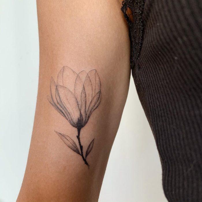 Tatuaje al estilo hand poke de capullo de una flor abriéndose en la parte interna del brazo