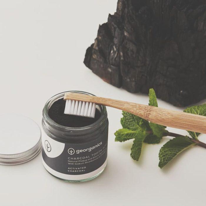 Recipiente con carbón activado y un cepillo de dientes