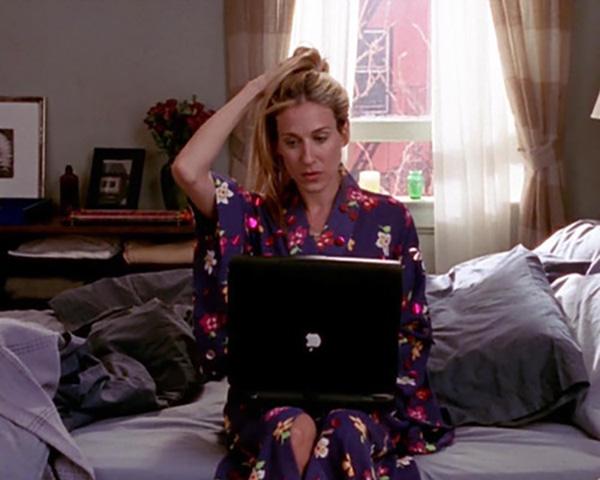 Carrie Bradshaw sentada en la cama con un kimono de flores morado