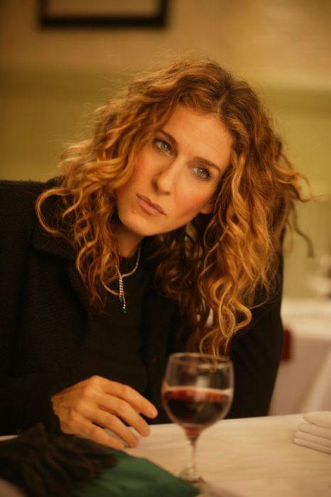 Carrie Bradshaw pesantiva tomando una copa de vino