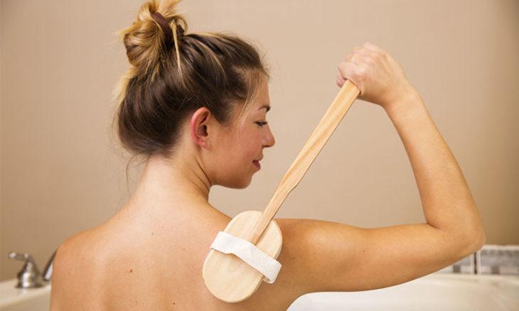 Mujer cepillando su piel con cepillo de cerdas suaves