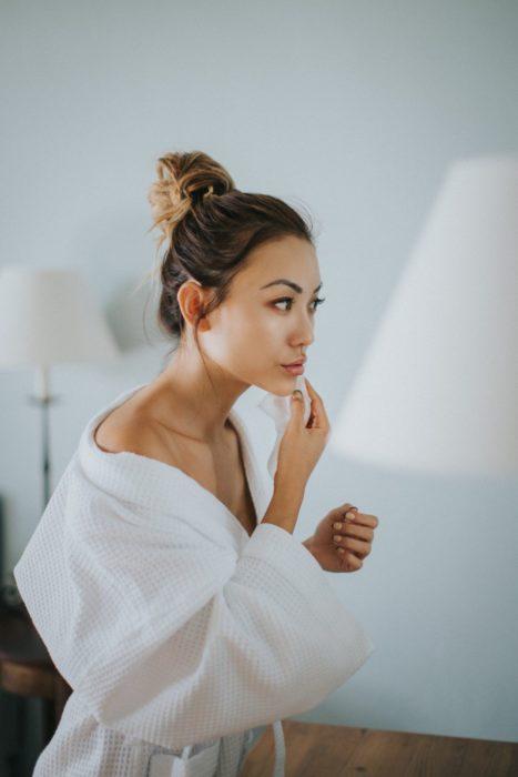 Chica en bata limpiando su rostro