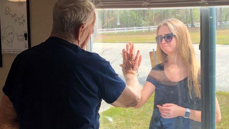 Chica poniendo su mano a través de una ventana