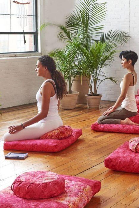Chicas meditando en sala de meditación