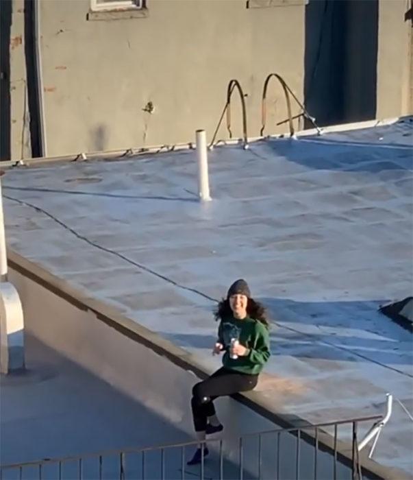 Chica sentada en el techo de su casa recibiendo un dron de un chico