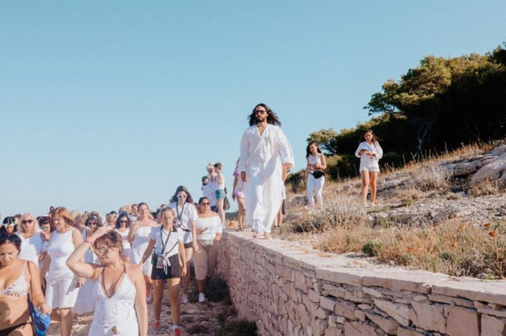 Jared Leto vestido de blanco caminando con sus fans, culto