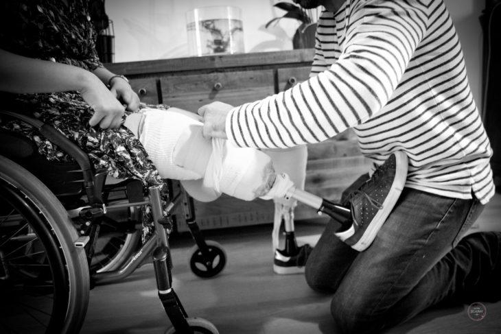 Sandrine en silla de ruedas y le ayudan a colocarse las protesis de los pies