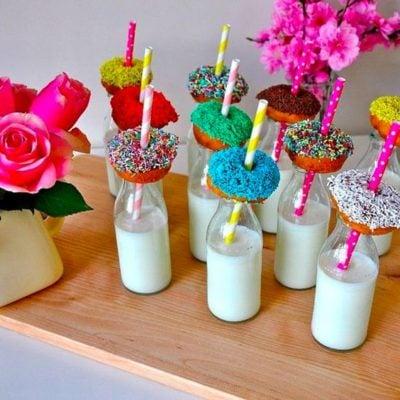 vasos de vidrio con leche y donas de colores como refrigerio para fiesta infantil