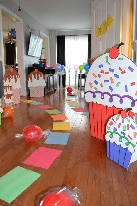 Camino con papeles de colores y decoración de cupcakes de cartón para fiesta infantil