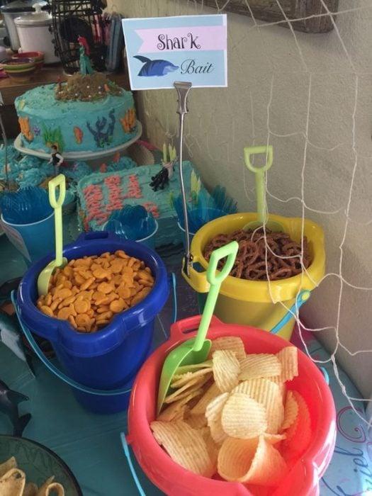 cubetas de plástico de colores con botanas para fiesta infantil