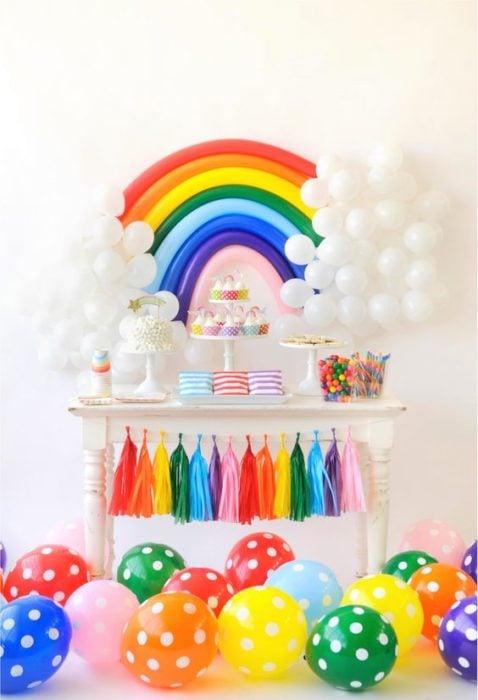 Mesa de dulces adornada con globos de colores con forma de arcoíris y globos blancos como nubes