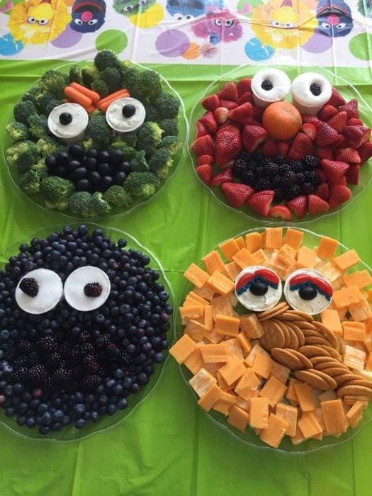Platos con verduras y snacks con formas de caras para fiestas infantiles