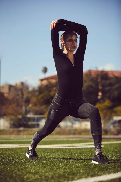 Chica con ropa deportiva realizando ejercicio al aire libre
