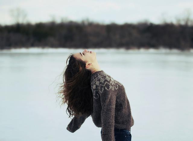 Mujer de cabello largo extiende sus brazos hacia abajo en una nieve